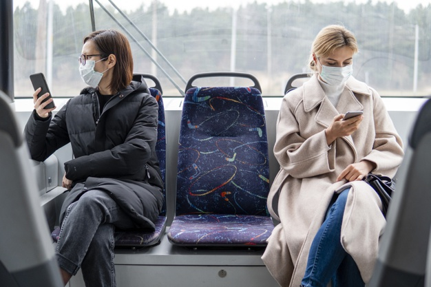 young-women-using-public-transport-with-surgical-mask_23-2148454309